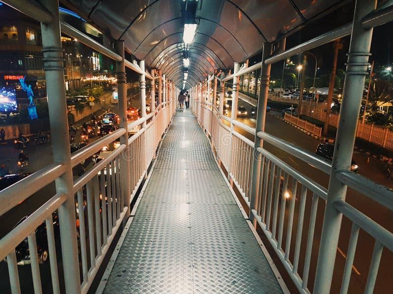 在拥挤街道中间的空的步行桥 免版税库存图片