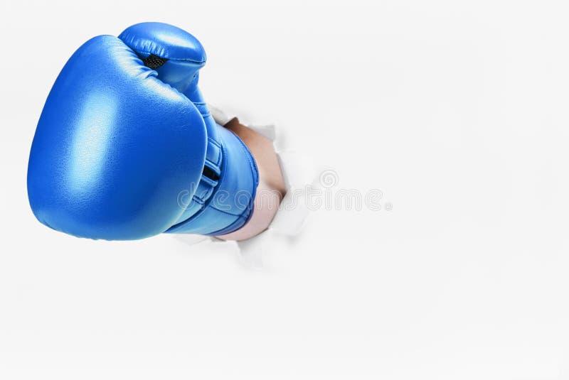 在拳击手套的手打破了纸墙壁 免版税库存图片