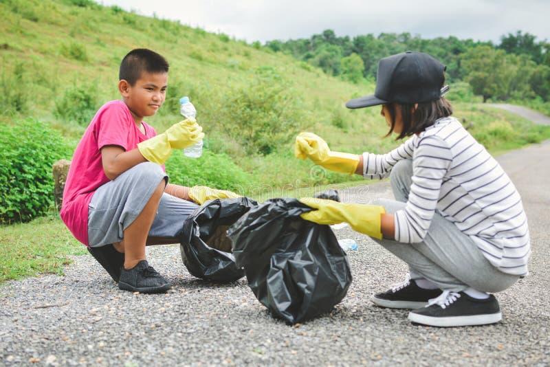 在拾起空瓶塑料的黄色手套的儿童手入容器袋子 图库摄影