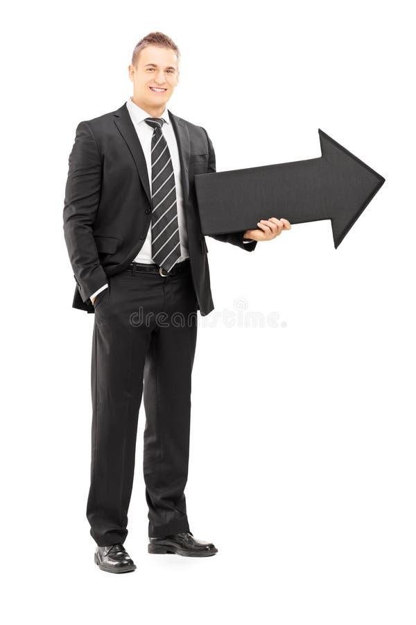 在拿着一个大箭头的黑衣服的微笑的商人 免版税库存图片
