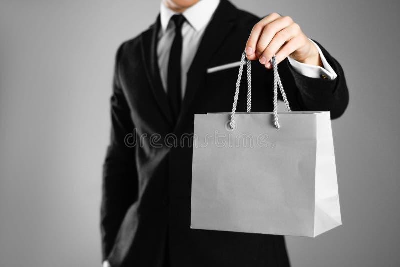 在拿着一个灰色纸礼物袋子的一套黑衣服的商人 关闭 被隔绝的背景 免版税图库摄影