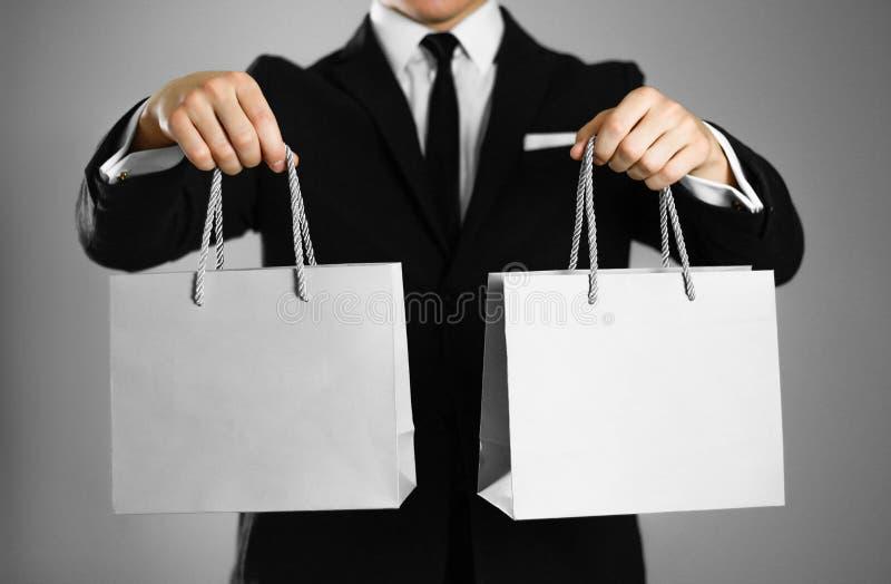 在拿着一个灰色纸礼物袋子的一套黑衣服的商人 关闭 被隔绝的背景 库存图片