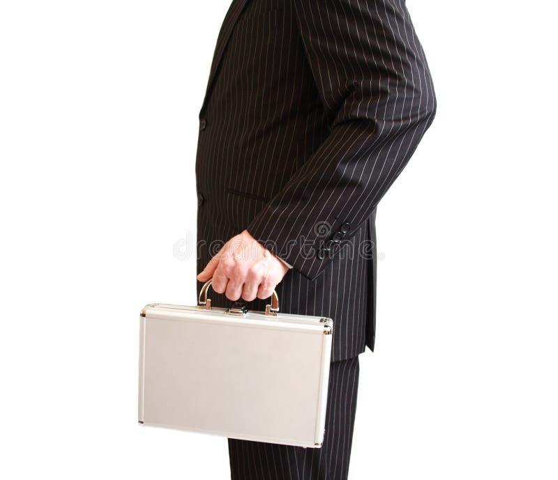 在拿着一个空白手提箱的黑色诉讼的生意人 库存照片