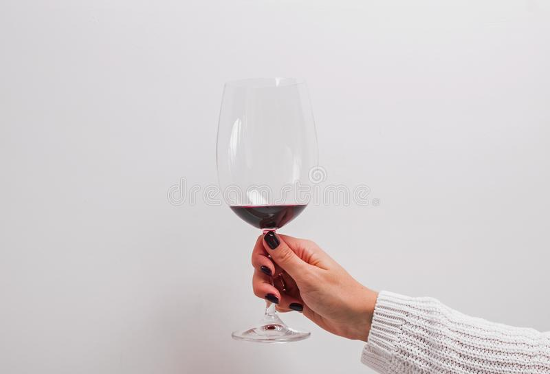 在拿着一杯红酒的一件白色毛线衣的妇女的手 免版税库存图片