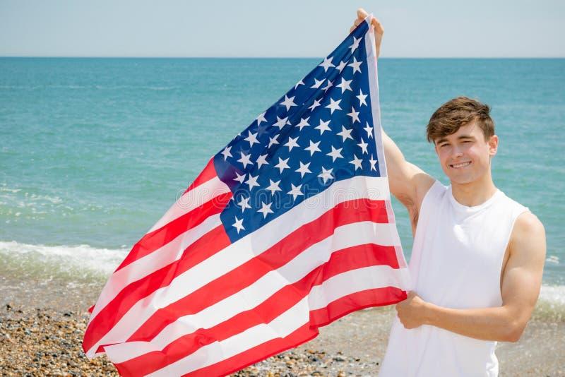 在拿着一面美国国旗的海滩的白种人男性 库存照片
