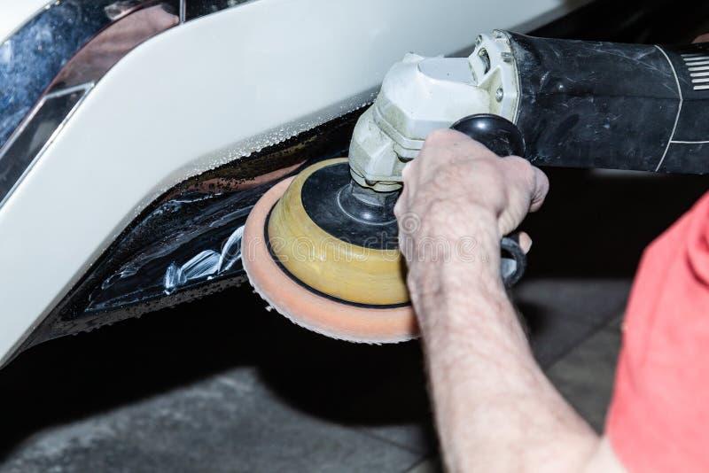 在拿着为擦亮汽车防撞器的一个工具,当工作在车时一名男性工作者的手上的特写镜头视图 库存图片