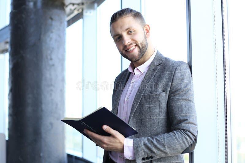 在拿着他的笔记本和看照相机的便服的悦目商人,当站立在办公室时 库存图片
