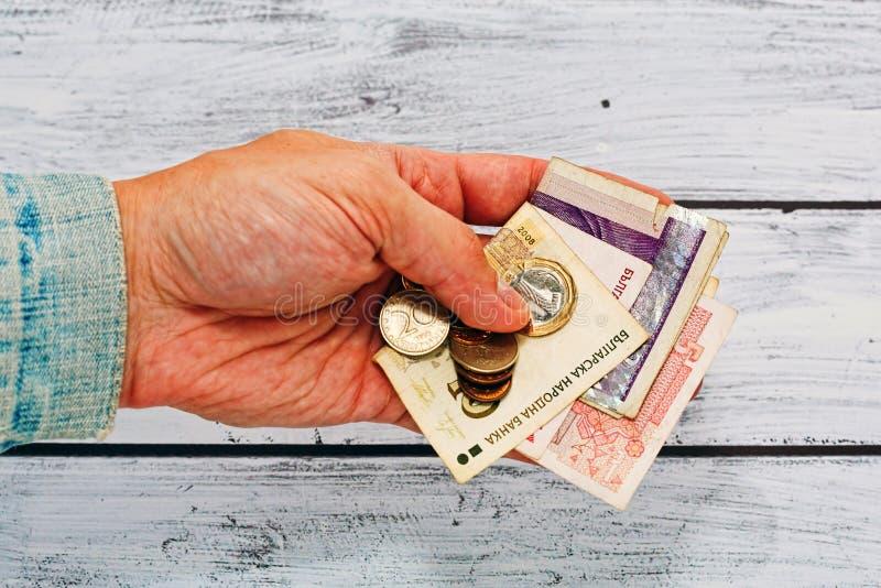 在拿着保加利亚的金钱的老夹克的男性手 免版税图库摄影