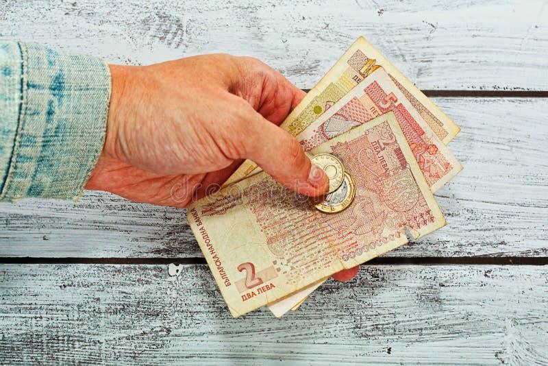 在拿着保加利亚金钱的牛仔裤夹克的男性手 免版税图库摄影