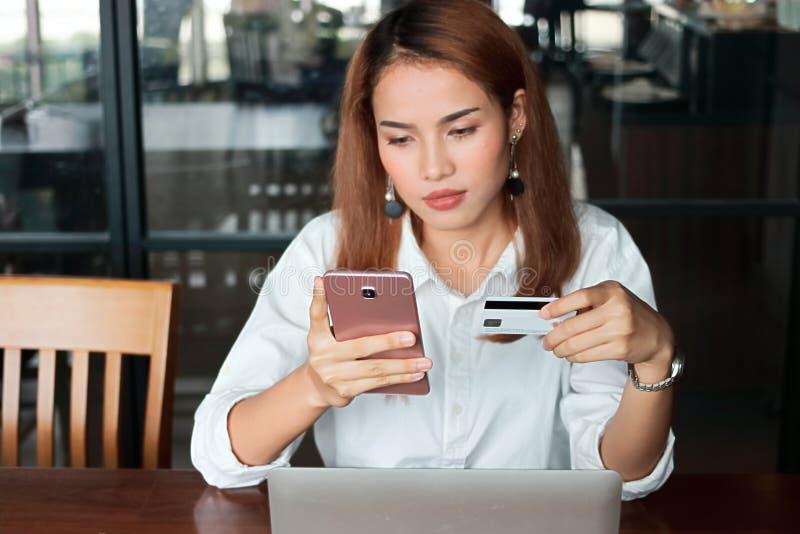 在拿着信用卡和流动巧妙的电话的年轻亚裔妇女的手上的选择聚焦在客厅 在线购物概念 免版税库存图片