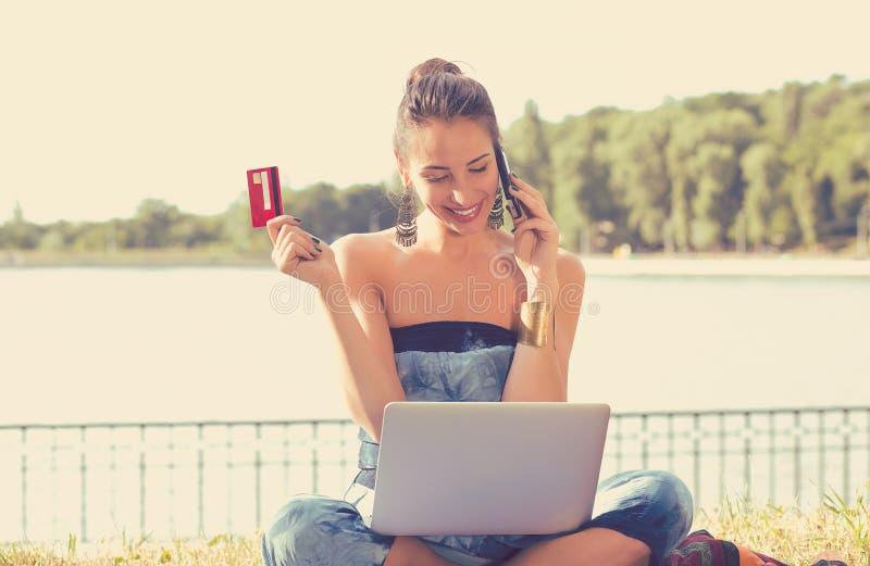 在拿着信用卡的线的妇女购物谈话在手机 免版税库存图片