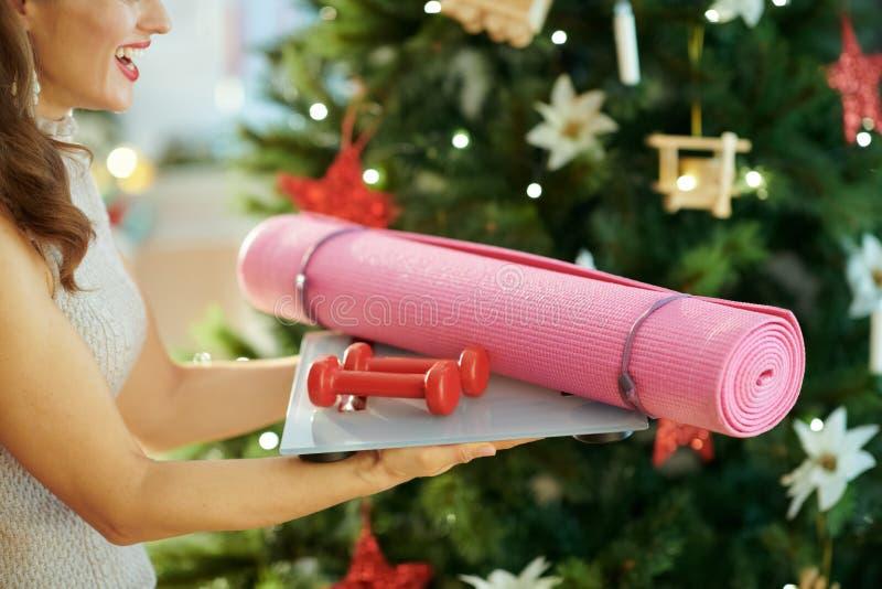 在拿着健身齿轮的圣诞树附近的年轻女人 免版税库存图片