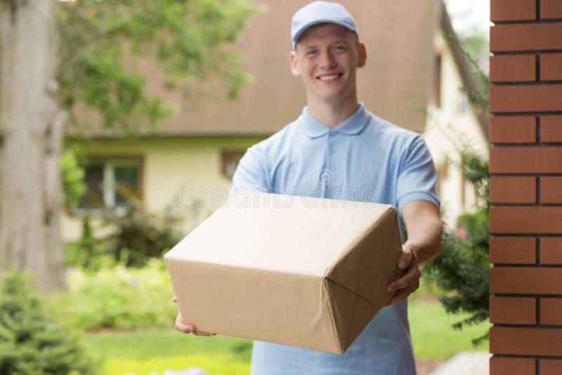 在拿着包裹的蓝色制服的年轻传讯者 免版税库存图片