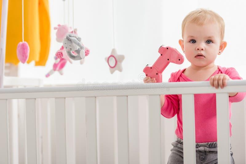 在拿着在小儿床和看的桃红色衬衣的可爱的孩子桃红色控制杆 库存图片