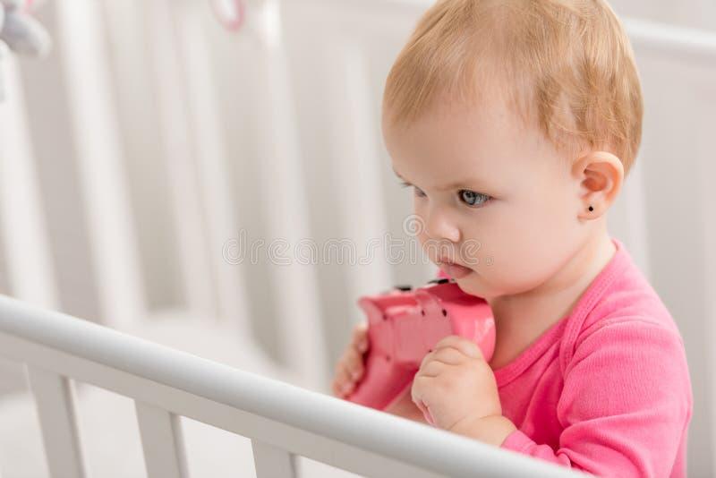 在拿着在小儿床的桃红色衬衣的可爱的孩子桃红色控制杆和 免版税库存照片