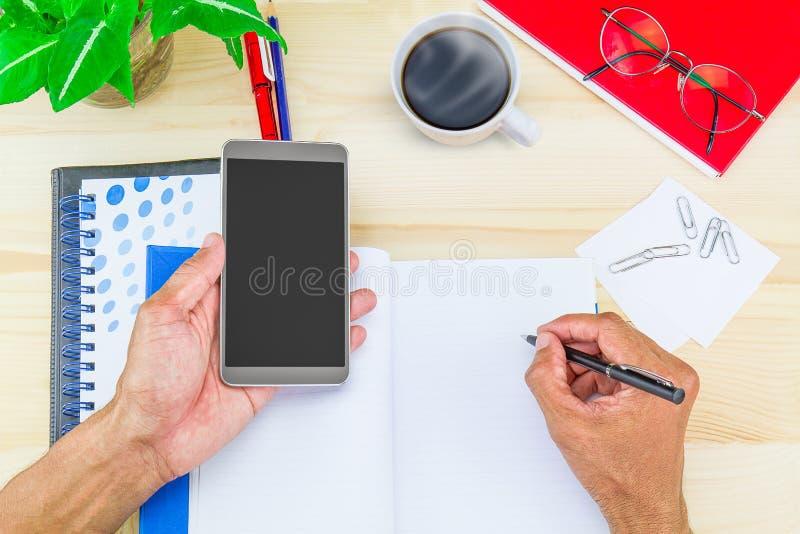在拿着在木书桌上的笔记本和左手的右手文字智能手机有热的咖啡杯的,办公用品,玻璃 免版税库存图片