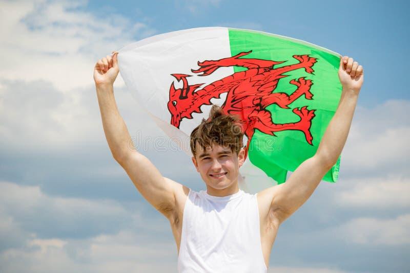 在拿着威尔士旗子的海滩的白种人男性 免版税库存照片