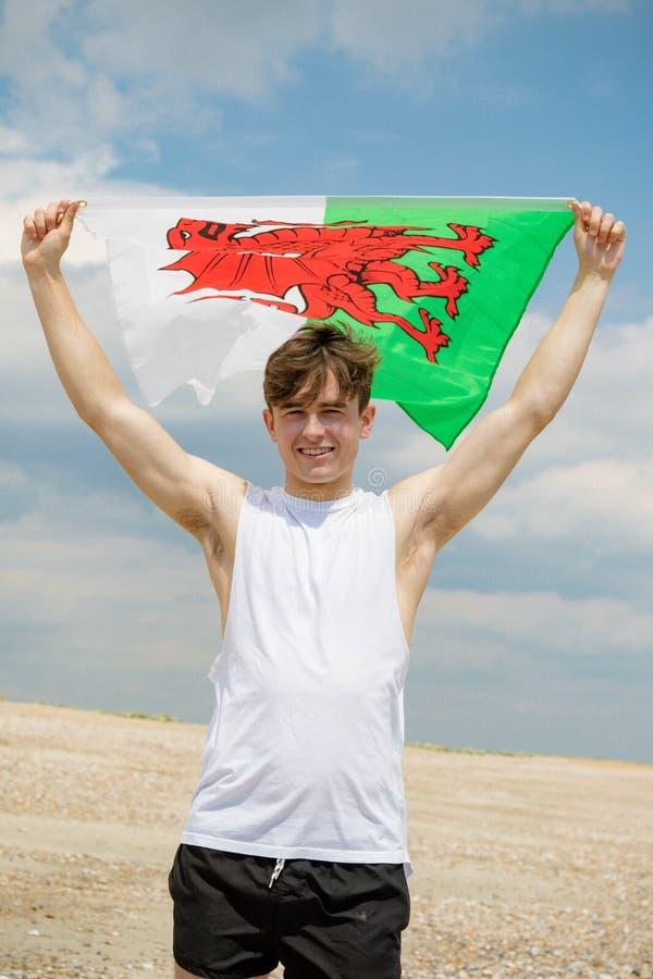 在拿着威尔士旗子的海滩的白种人男性 免版税库存图片