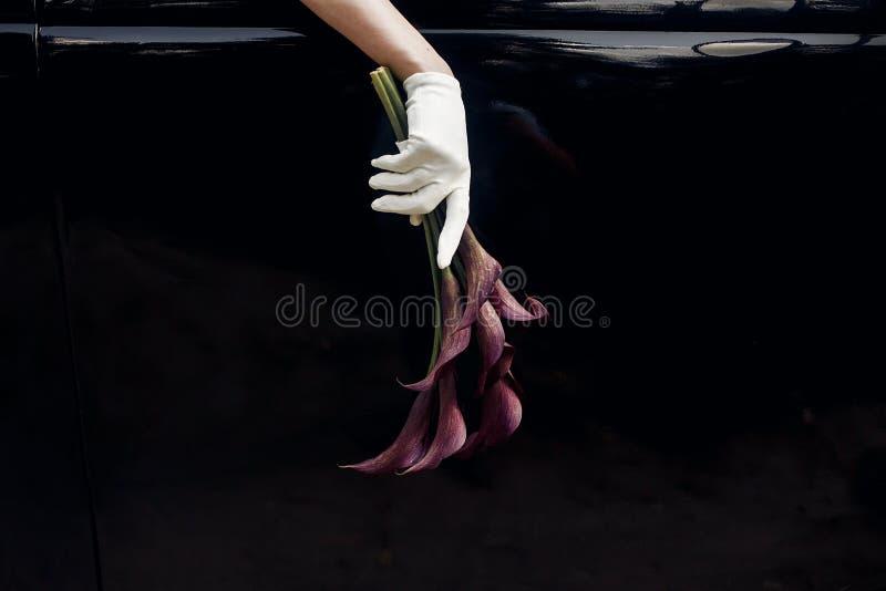 在拿着婚礼bouque的丝绸手套的典雅的华美的新娘手 免版税库存图片