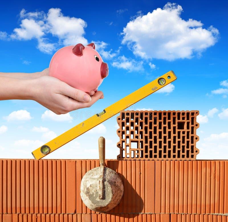 在拿着存钱罐的砖墙和手上的石工工具 库存图片
