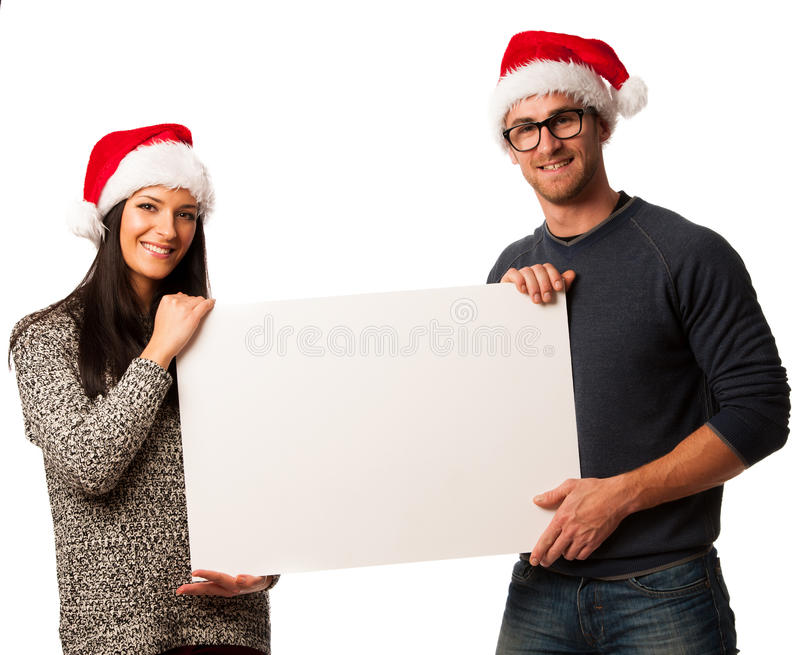 在拿着广告的圣诞老人帽子的年轻夫妇空白的委员会 图库摄影