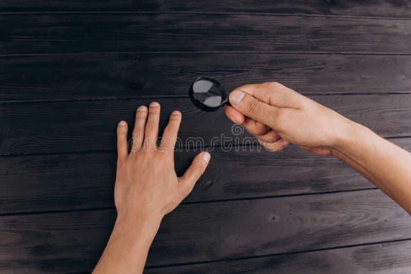 在拿着放大镜的一张土气黑书桌上的人的手 指纹考试 棕榈特写镜头 免版税库存照片