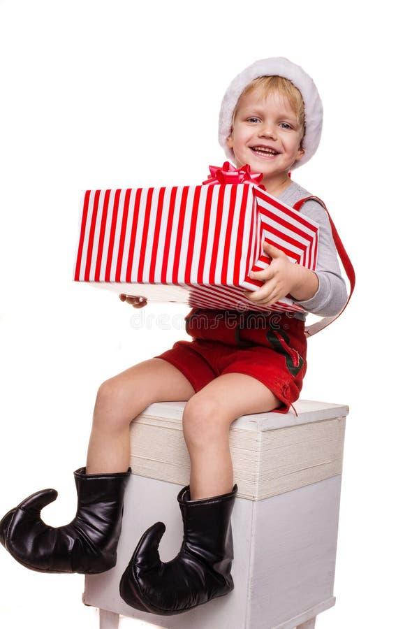 在拿着有丝带的矮人红色服装的小白肤金发的孩子大礼物盒 圣诞节概念 库存照片