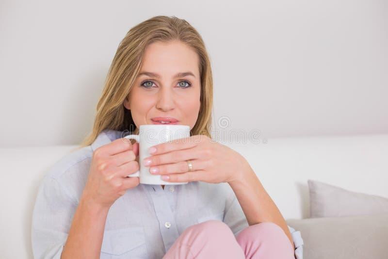 在拿着杯子的长沙发的美满的偶然白肤金发的开会 免版税库存图片