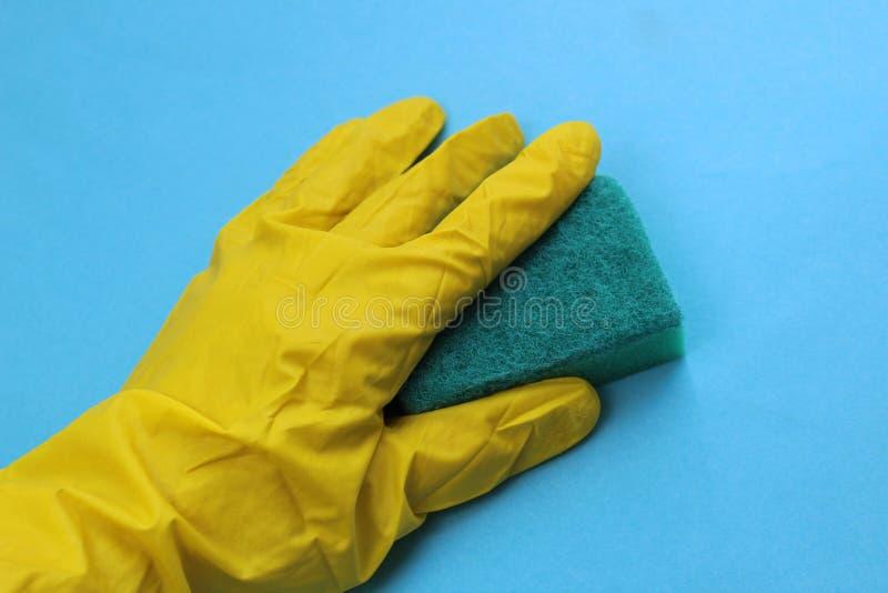 在拿着洗涤的黄色橡胶手套的手一块海绵 免版税库存照片
