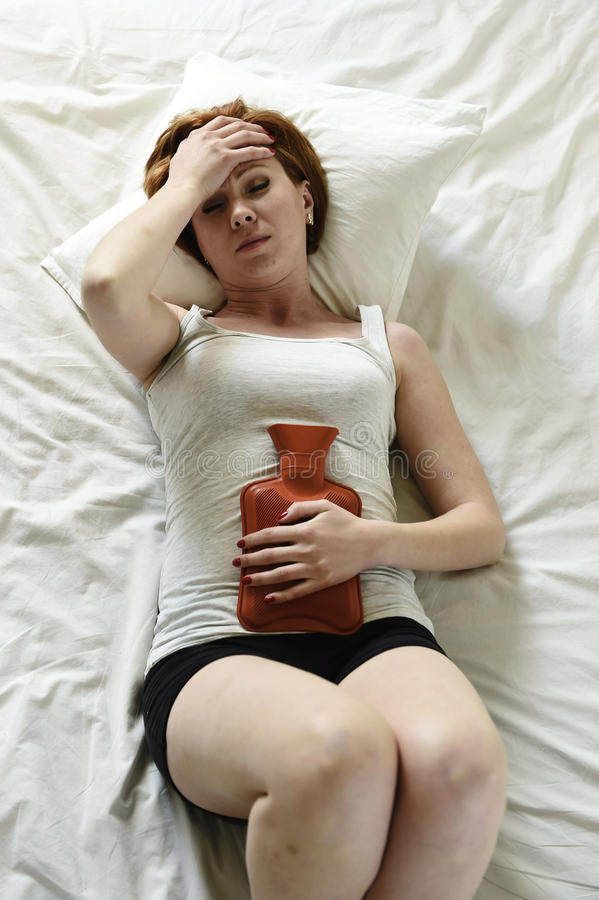 在拿着热水袋的腹部的少妇遭受的胃痉挛反对肚子 免版税库存图片