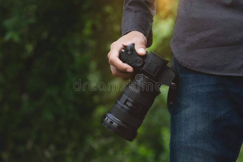 在拿着照相机的摄影师手上的特写镜头 免版税库存图片