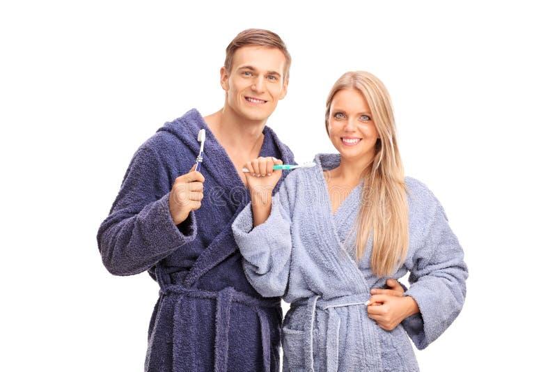 在拿着牙刷的蓝色浴巾的年轻夫妇 免版税库存照片