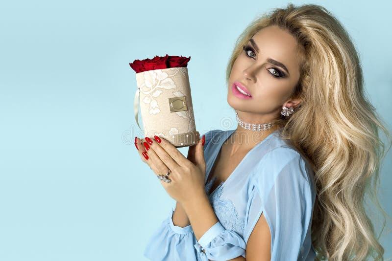 在拿着玫瑰的花束庄重装束的美好的白肤金发的模型,花箱子 华伦泰的和生日礼物在蓝色背景 库存照片