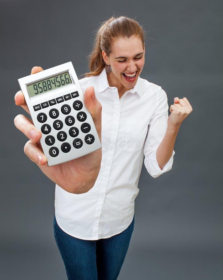 在拿着符号计算器的激动的美丽的少妇赢取的金钱 免版税图库摄影