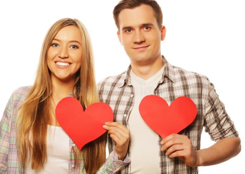 在拿着红色心脏的爱的愉快的夫妇 免版税库存照片