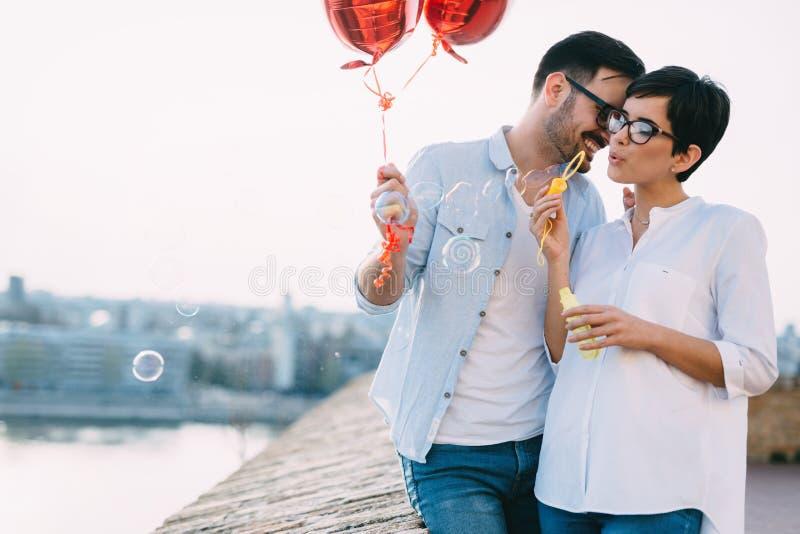 在拿着红色baloons心脏的爱的夫妇在情人节 免版税库存照片