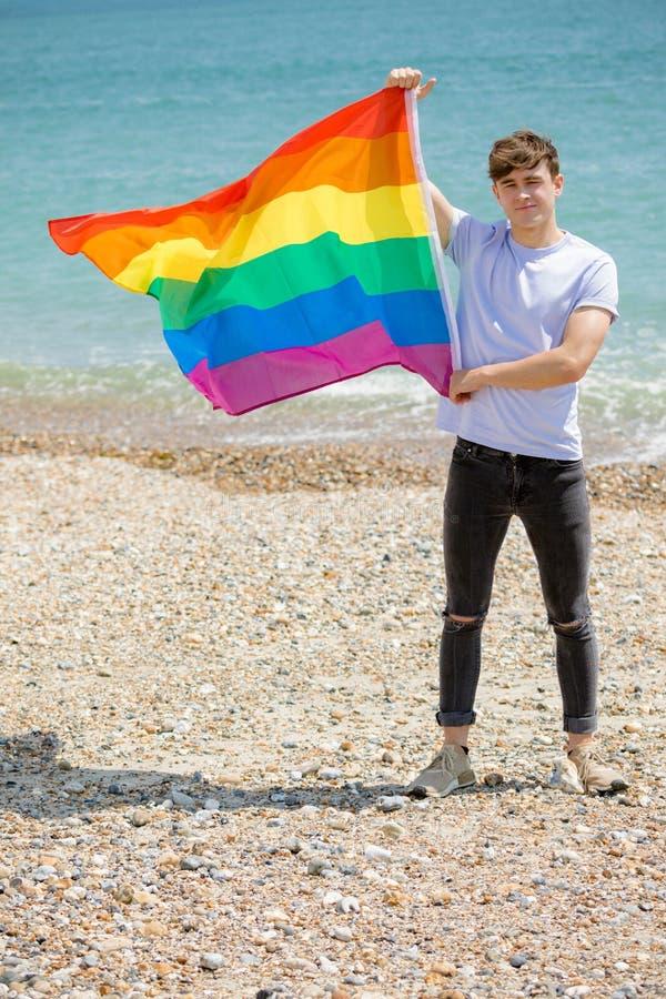 在拿着自豪感旗子的海滩的白种人男性 库存图片