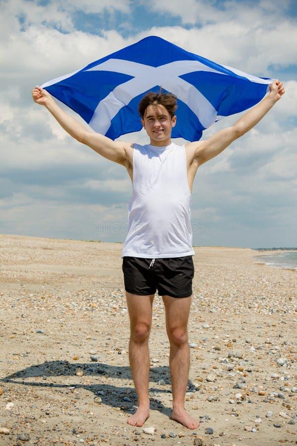 在拿着苏格兰旗子的海滩的白种人男性 免版税库存照片