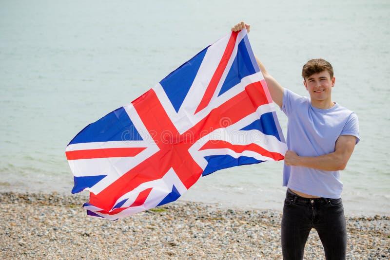 在拿着英国旗子的海滩的白种人男性 免版税库存照片