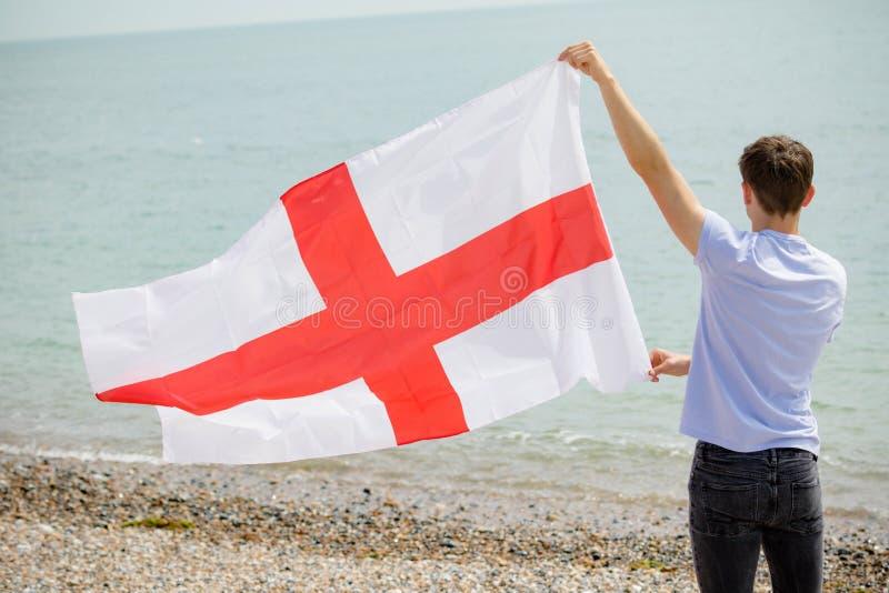 在拿着英国旗子的海滩的白种人男性 免版税库存图片