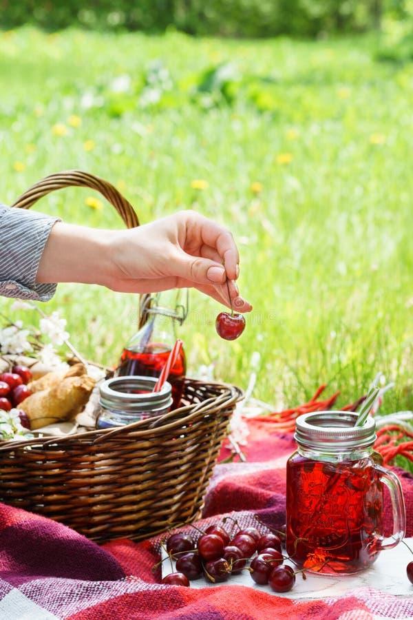 在拿着莓果的金属螺盖玻璃瓶和年轻女人手的樱桃汁 库存图片