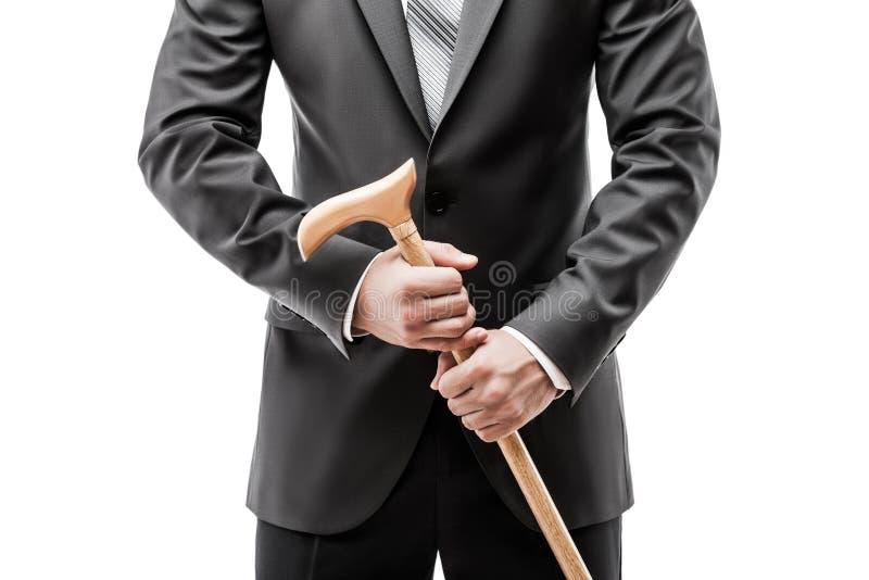 在拿着走的藤茎棍子的黑衣服的商人 免版税库存图片