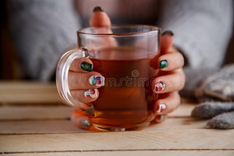 在拿着透明杯茶的一件灰色夹克的妇女的手 正面图 在一张轻的葡萄酒木桌上 免版税库存图片