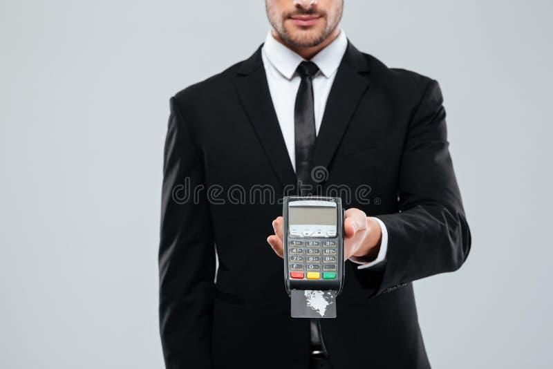在拿着银行的黑衣服的商人终端与信用卡 免版税库存图片