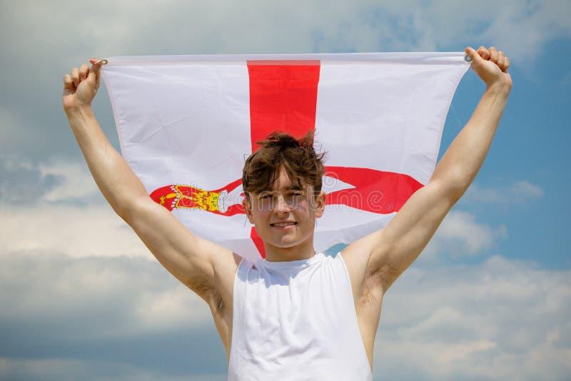 在拿着阿尔斯特旗子的海滩的白种人男性 库存照片