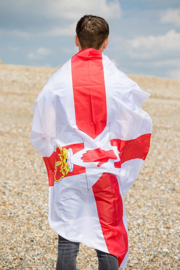 在拿着阿尔斯特旗子的海滩的白种人男性 免版税库存照片