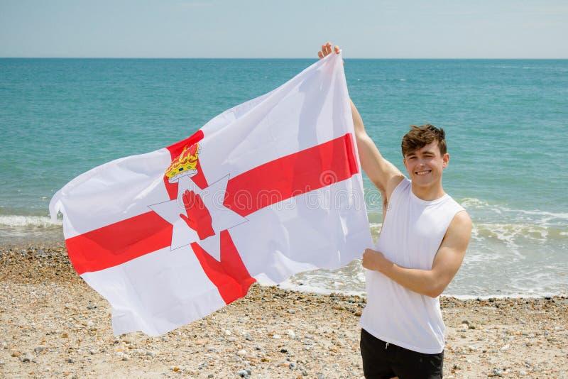 在拿着阿尔斯特旗子的海滩的白种人男性 库存图片