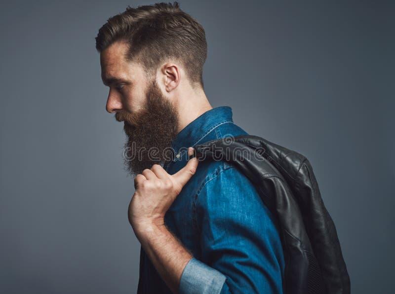 在拿着黑夹克的有胡子的人的侧视图 免版税库存图片
