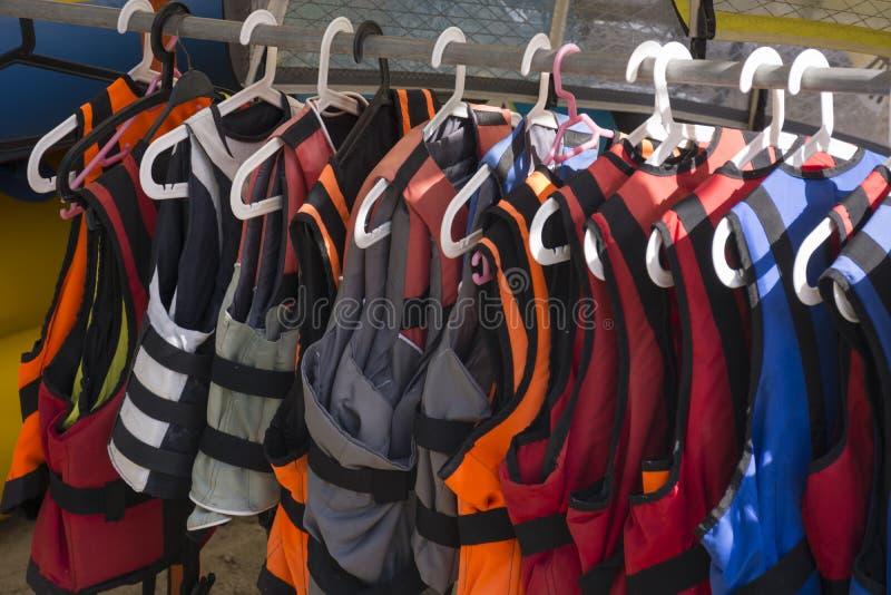 在挂衣架特写镜头的救生衣 五颜六色的救生背心 图库摄影
