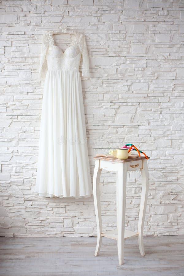 在挂衣架白色砖墙上的美丽的婚礼礼服 库存图片
